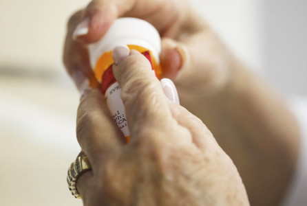 Senior citizen woman with arthritic hands struggling to get the prescription cap open.