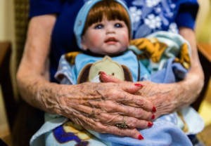 Vivian Guzofsky, 88, holds a baby doll at Sunrise Senior Living in Beverly Hills, Calif. Guzofsky, who has Alzheimer's disease, is calm when taking care of the dolls. Heidi de Marco/Kaiser Health News