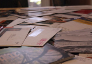 This table is covered with mail envelopes and solicitations. Identifiers have been blurred out.