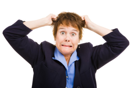 Mature business woman overwhelmed with frustration, pulling her hair. frustrated Isolated on white.