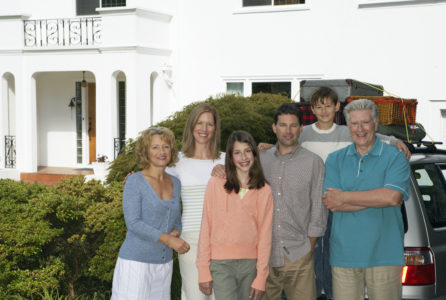 Family group standing in front drive outside house, smiling, portrait