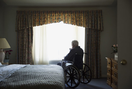 Senior man in wheelchair looking through bedroom window