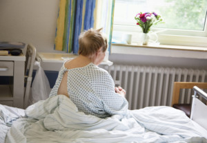 senior woman, sitting on bed in hospital, back view