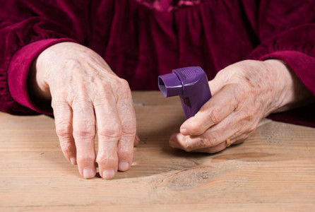 Senior woman's hands holding asthma inhaler