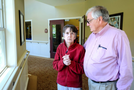 Bill Harris visits his wife, Nora, at the Fern Gardens memory care center in Medford, Ore. Nora Harris was diagnosed with early-onset Alzheimer's disease in 2009. Now 64, she can no longer communicate or recognize family and friends. She signed an advance directive stipulating no care to prolong her life, but her husband says state law is forcing her to be spoon-fed against her stated wishes. (Jim Craven for KHN)