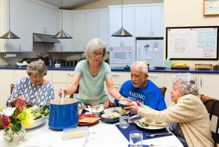 Cohousing:Carolyn Langenkamp, 68, helps serve the family-style dinner on Oct. 23, 2017. (Heidi de Marco/KHN)