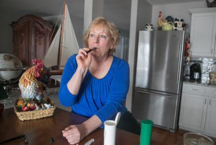 Ann Marie Owen uses her marijuana vaporizer at home in Port Ewen, N.Y., on Feb. 19, 2018. Owen has transverse myelitis, and when New York legalized marijuana for the treatment of select medical ailments, she decided it was time to swap pills for pot. But her doctors refused to help. (Allyse Pulliam for KHN)