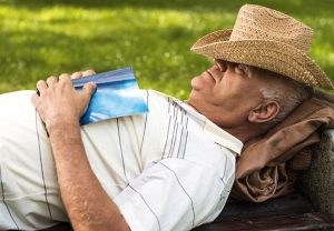 Old man napping on a bench at the park and sleeping with hat on his head.