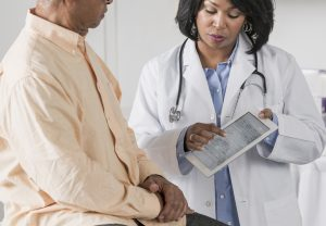 African American doctor showing patient digital tablet