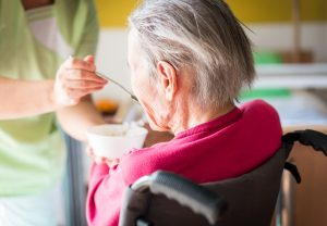 Nursing and feeding senior sick woman in wheelchair