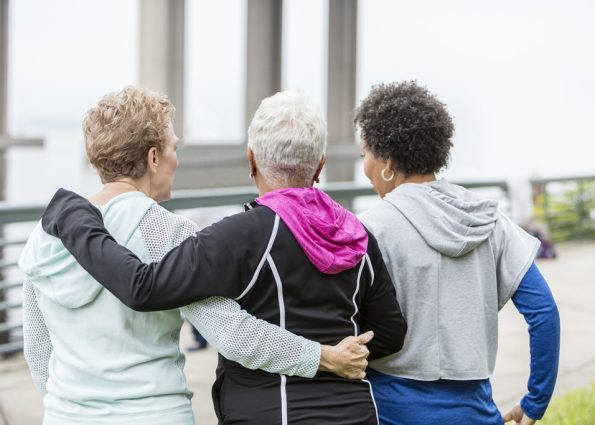 Rear view of three multi-ethnic women wearing hooded sweatshirts, hanging out together in the city, standing side by side with arms around each other. The woman with black hair is in her 50s and her senior friends are in their 60s.