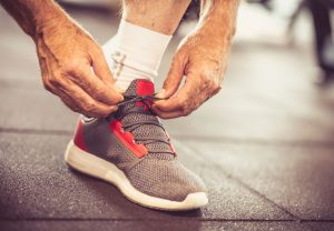 Sportsman tying sneakers and preparation for exercise. Close up.