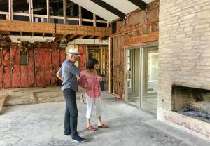 Chris and Dennis Cavner of Austin, Texas, stand in the sunken living area of the 1974 single-story home they bought in February. In the remodel, the Cavners are raising and leveling the floor for easier aging in place without steps. (Sharon Jayson for Kaiser Health News)