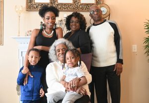 "The Walker family ― (standing from left) Michael ""Amir"" Nimrod, Andre'a Walker-Nimrod, Wilma Walker, Howard Walker, (seated) matriarch Evelyn Whitfield and Maleeya Nimrod ― pose for a portrait at the Walker residence on March 21, 2020, in Florissant, Missouri. (Photo by Michael B. Thomas for KHN)"