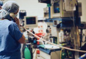 Nurse in scrubs, talking on phone in operating room, rear view