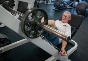 "Art Ballard loads a 25-pound plate onto the leg press. ""At my age, the best thing you can do is find a routine."""