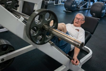 """Art Ballard loads a 25-pound plate onto the leg press. """"At my age, the best thing you can do is find a routine."""""""